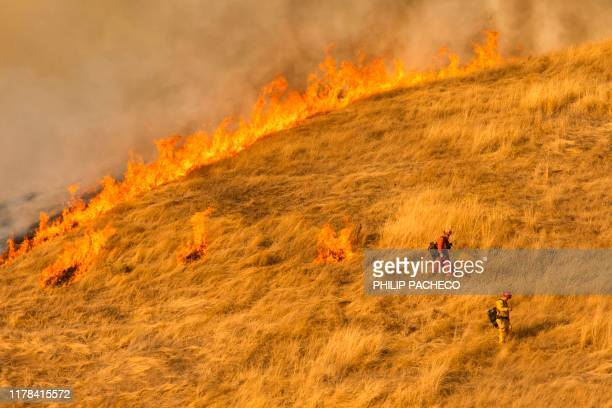 Firefighters set a back fire along a hillside near during firefighting operations to battle the Kincade Fire in Healdsburg California on October 26...