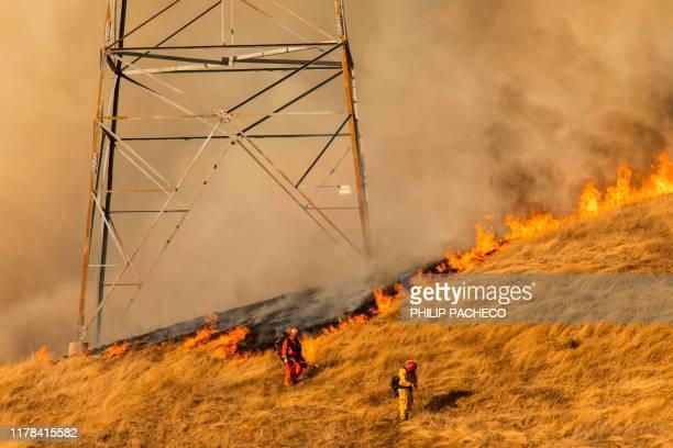 TOPSHOT Firefighters set a back fire along a hillside near PGE power lines during firefighting operations to battle the Kincade Fire in Healdsburg...