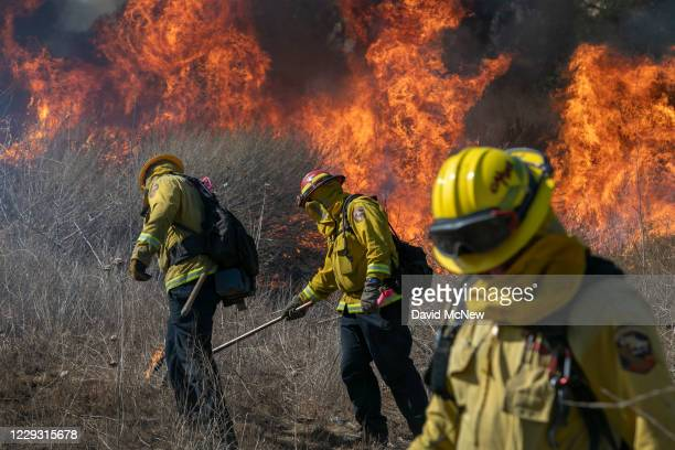 Firefighters set a backfire to protect homes and to try to contain the Blue Ridge Fire on October 27, 2020 in Chino Hills, California. Strong Santa...