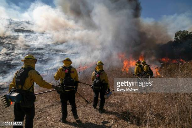 Firefighters set a backfire to protect homes and try to contain the Blue Ridge Fire on October 27, 2020 in Chino Hills, California. Strong Santa Ana...