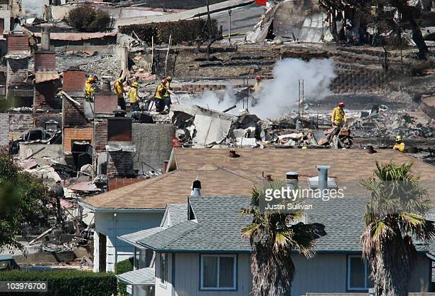 Firefighters sift through rubble at a burned home that was destroyed by a massive explosion and fire September 10 2010 in San Bruno California Thirty...