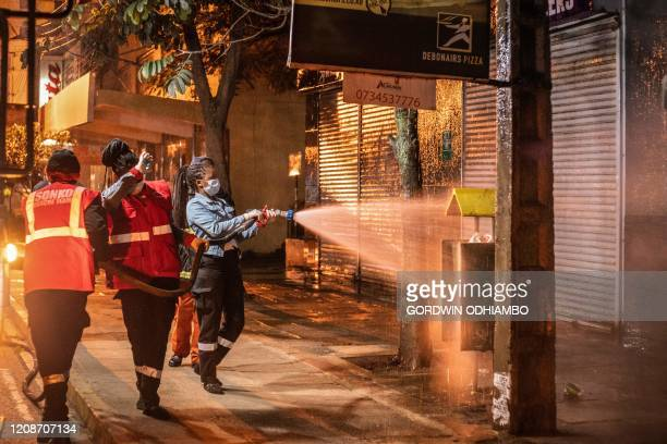 Firefighters spray disinfectant on a street during the night curfew to curb the spread of the COVID19 coronavirus in Nairobi Kenya on March 30 2020...