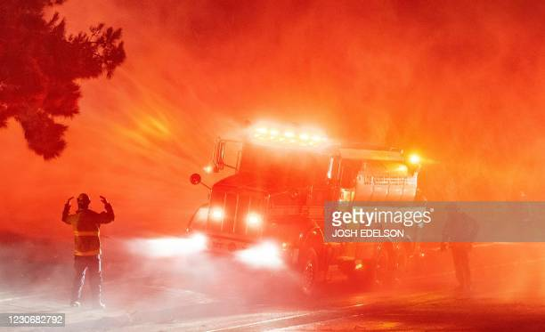 Firefighters spray down flames on the side of Interstate 210 in Sylmar, California on January 19, 2021. - Dozens of fires ignited as high winds and...