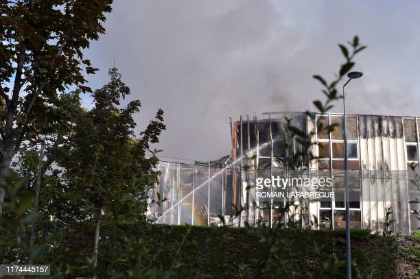 Firefighters spray liquid from a hose as they attempt to control a factory fire in Villeurbanne, central-eastern France on October 8, 2019. - A large...