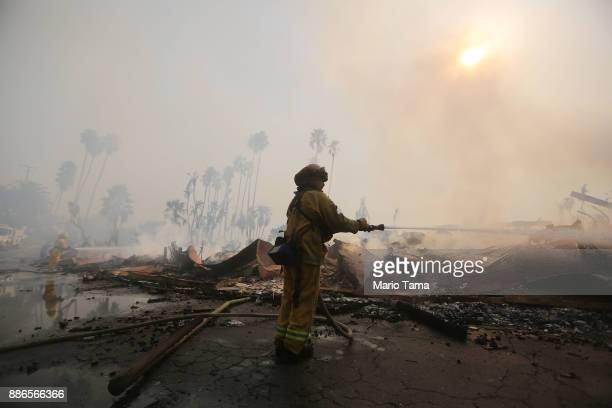 Firefighters spray water at the remains of an apartment complex destroyed by the Thomas Fire on December 5 2017 in Ventura California Around 45000...
