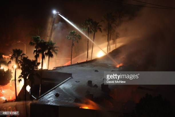 Firefighters spray water on a burning commercial structure at the Poinsettia fire one of nine wildfires fueled by wind and record temperatures that...