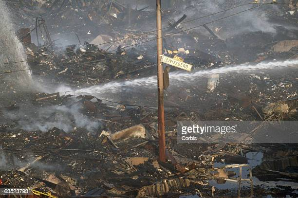 Firefighters spray water on charred rubble in the Marina District after the 1989 San Francisco earthquake