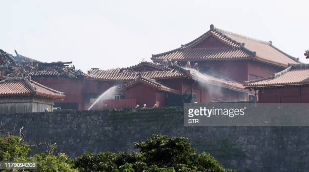 Firefighters spray water on Shuri Castle after a fire ripped through the historic site in Naha Okinawa prefecture southern Japan on October 31 2019 A...