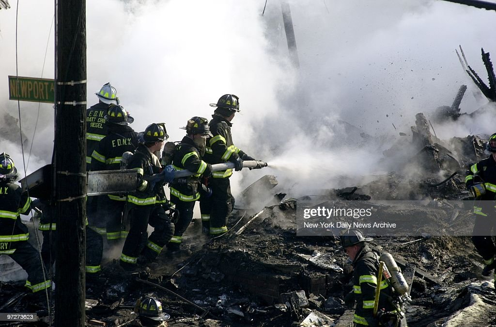 Firefighters spray water on smoldering remains of American A : Fotografia de notícias