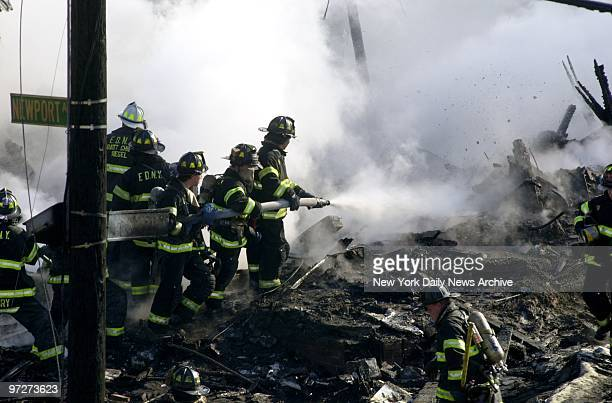 Firefighters spray water on smoldering remains of American Airlines flight 587 after it crashed in the Rockaway section of Queens