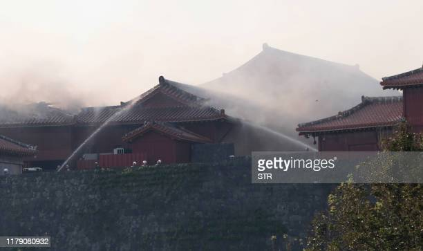 Firefighters spray water on the Shuri Castle in Naha Okinawa prefecture southern Japan on October 31 2019 A fire ripped through the ancient Japanese...
