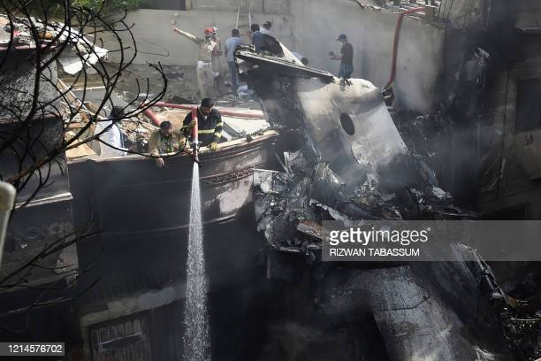 Firefighters spray water on the wreckage of a Pakistan International Airlines aircraft after it crashed at a residential area in Karachi on May 22,...