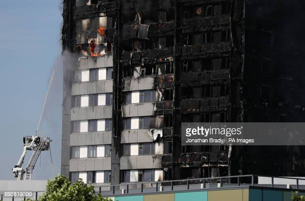 Firefighters spray water onto a fire that engulfed the 24storey Grenfell Tower in west London