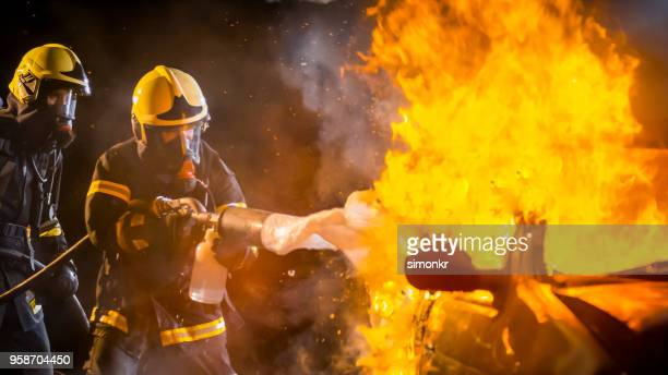 firefighters spraying firefighting foam on burning car - extinguishing stock pictures, royalty-free photos & images