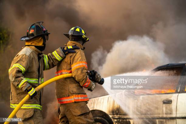 2 firefighters spraying high pressure water to fire - firefighter stock pictures, royalty-free photos & images