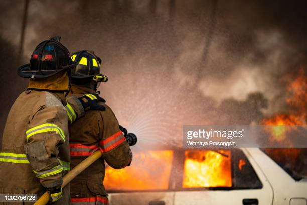 firefighters spraying water on burning car - fire protection suit stock pictures, royalty-free photos & images