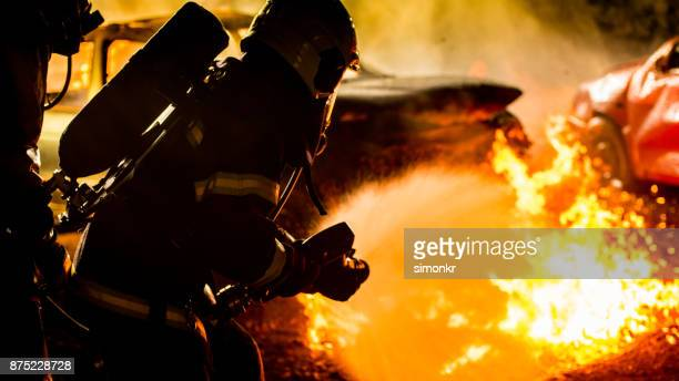 firefighters spraying water on burning car - firefighter's helmet stock photos and pictures