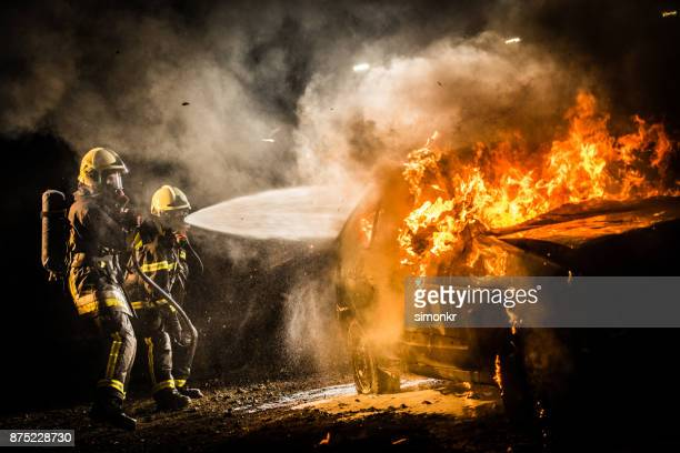 firefighters spraying water on burning car - fire protection suit stock photos and pictures