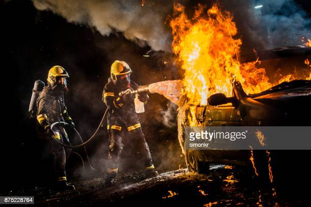 firefighters spraying water on burning car - firefighter stock pictures, royalty-free photos & images