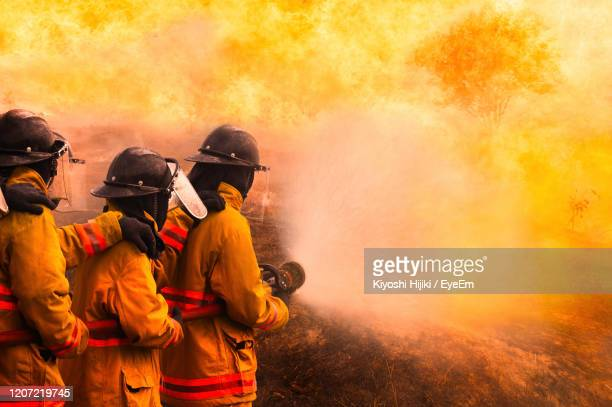firefighters spraying water on fire - firefighter stock pictures, royalty-free photos & images