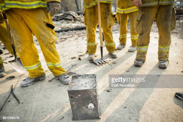 Firefighters stand around a safe recovered from the remains of a home in the Fountaingrove neighborhood on October 13, 2017 in Santa Rosa,...