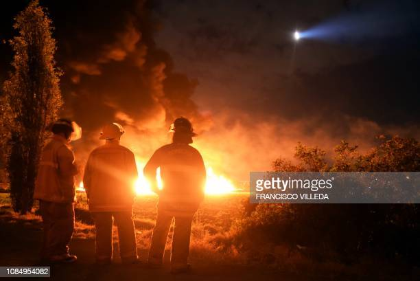 TOPSHOT Firefighters stand at the scene of a massive blaze trigerred by a leaky pipeline in Tlahuelilpan Hidalgo state Mexico on January 18 2019 An...