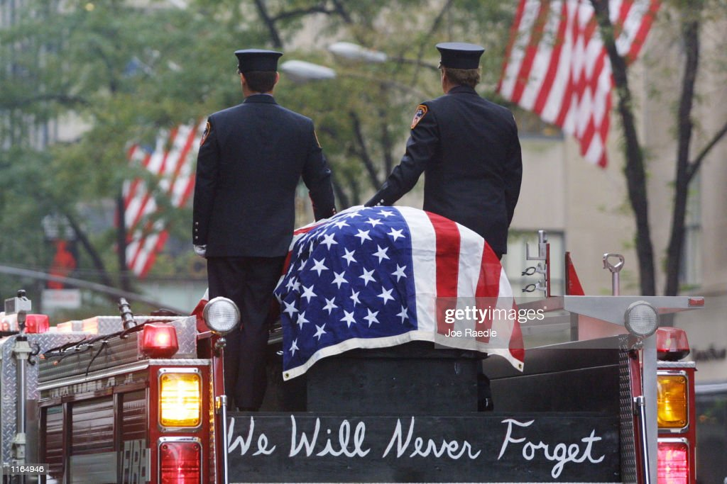 Firefighters stand atop a fire engine with the flag draped casket of fellow fireman Lt. Dennis Mojica September 21, 2001 during a funeral service at St. Patrick's Cathedral in New York City. Mojica, who was with Rescue Company 1, is one of nearly 300 firefighters who lost their lives in the World Trade Center disaster.