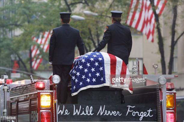 Firefighters stand atop a fire engine with the flag draped casket of fellow fireman Lt Dennis Mojica September 21 2001 during a funeral service at St...
