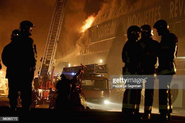 Firefighters stand by at a warehouse fire in the early hours on November 4 2005 in AulnaysousBois outside Paris France French authorities deployed...
