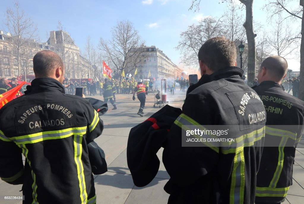 Firefighters stand during a demonstration of French firemen against staff reduction on the place de la Republique in Paris on March 14, 2017. / AFP PHOTO / Jacques DEMARTHON