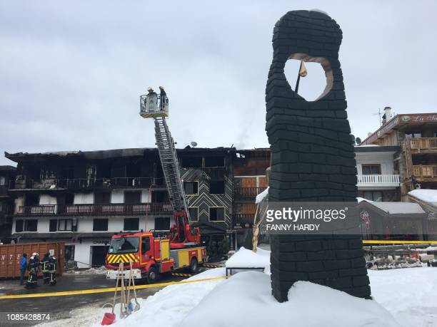 Firefighters stand in front of a building destroyed by a major fire which killed two people and injured 22 more on January 20 2019 at the ski resort...