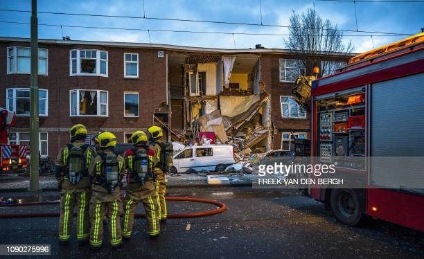 Firefighters stand in front of a partially collapsed building following an explosion cause unknown in The Hague on January 27 2019 Two people were...