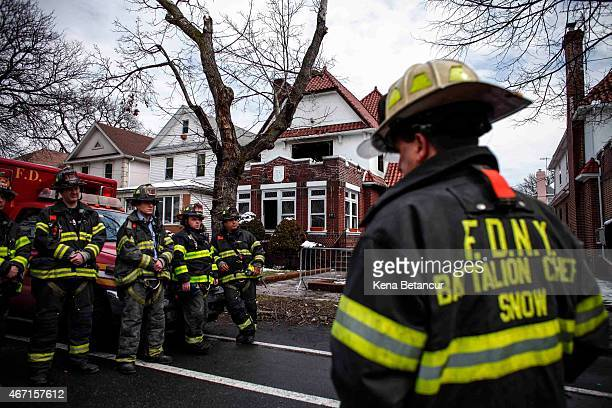 Firefighters stand in front of the House fire in the Midwood neighborhood in Brooklyn on March 21 2015 in New York City Seven children from the same...