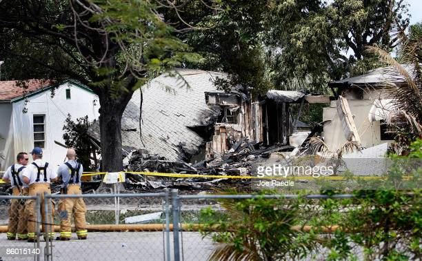 Firefighters stand near a home that was cut in half when a Cessna 421 twinengine propeller plane crashed into it shortly after takeoff from Fort...