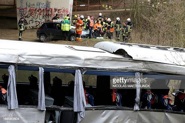 Firefighters stand near the wreckage of a bus after it crashed off the E34 highway near Ranst, Antwerp province, on April 14, 2013. At least five...