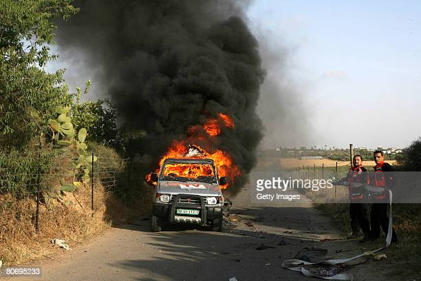 Firefighters stand next to burning car of Reuters cameraman Fadel Shaana after it was hit by an Israeli missile on April 16 2008 in central Gaza...