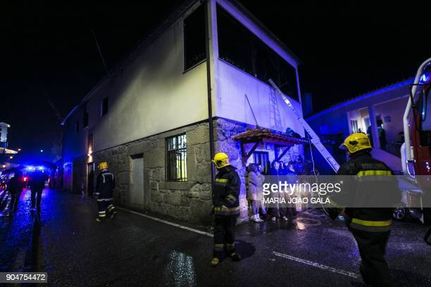 Firefighters stand outside the building of a local community centre where a fire killed eight people and injured 50 others in Vila Nova da Rainha in...