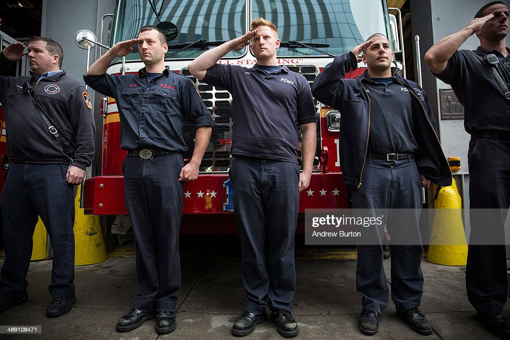 Firefighters stand to attention as emergency vehicles transporting the unidentified remains of victims of the September 11, 2001 attacks onto the World Trade Center site, where they will be kept at the 9-11 Museum on May 10, 2014 in New York City. The decision by city officials to keep the remains at the museum until they are able to be identified has drawn both support and criticism by families of victims. A protest was held by a small group of people in protest to the decision as the remains were moved early this morning.