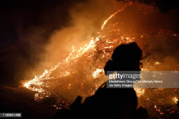 Firefighters stand watch by a fire line along Mayacama Club Drive as the Kincade Fire burns on the outskirts of Santa Rosa Calif on Oct 28 2019