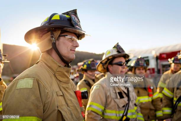 firefighters standing at fire station - firefighter stock pictures, royalty-free photos & images
