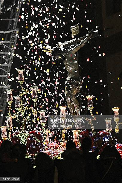 Firefighters standing on a crane throw flower petals on an effigy of Christ during the 'San Bernardo' brotherhood Easter procession in Sevilla on...