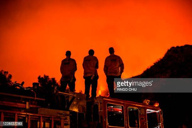 Firefighters standing on their fire truck watch as the Bobcat Fire burns on hillsides behind homes in Monrovia, California on September 15, 2020. - A...