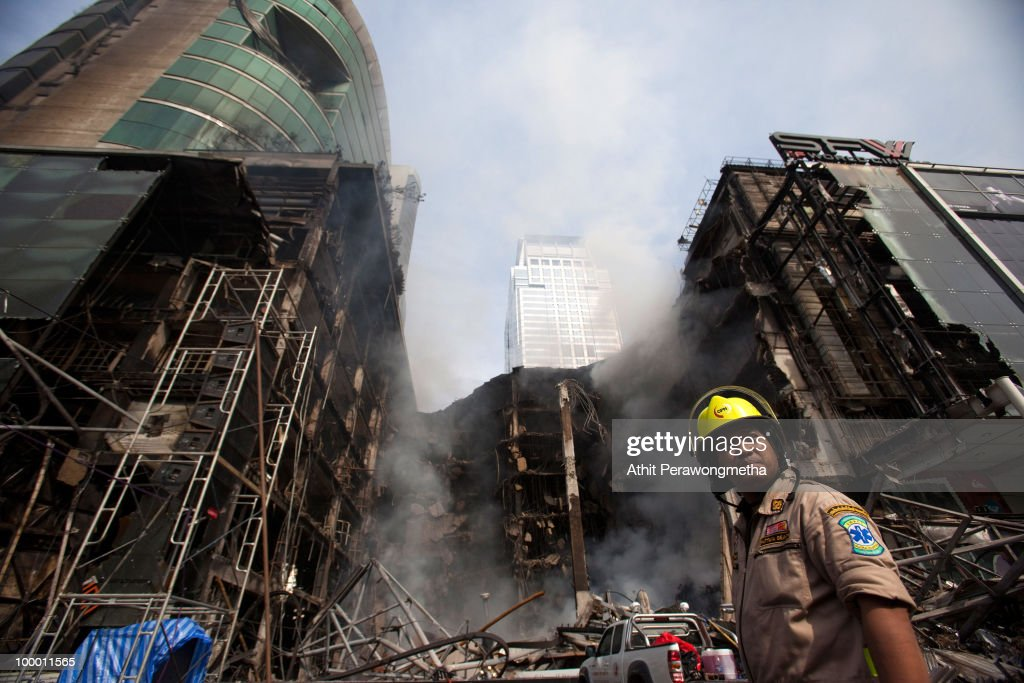 Firefighters stands next to the Central World Thailand's largest shopping complex as set on fire by Red Shirt anti-government protesters on May20, 2010 in Bangkok, Thailand. Thai authorities have extended curfews in the capital city and other provinces for three further nights. At least 44 people have been killed in clashes in which protesters clashed with military forces over a period of six consecutive days, resulting in the end of the blockade and the surrender of Red-shirt leaders.