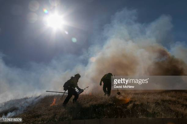 Firefighters step quickly to stay ahead of growing flames as they set a backfire to protect homes and try to contain the Blue Ridge Fire on October...