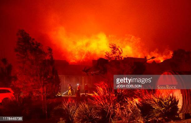TOPSHOT Firefighters survey Soda Rock Winery as it begins to burn during the Kincade fire in Healdsburg California on October 27 2019 Powerful winds...