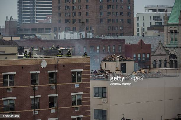 Firefighters survey the damage after a twobuilding collapse from the roof tops of an adjacent building on March 12 2014 in New York City Reports of...