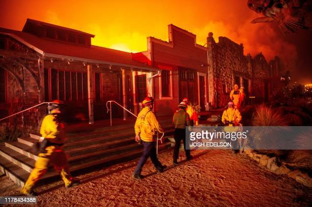 Firefighters survey the Soda Rock Winery as it burns during the Kincade fire as flames race through Healdsburg California on October 27 2019 Powerful...