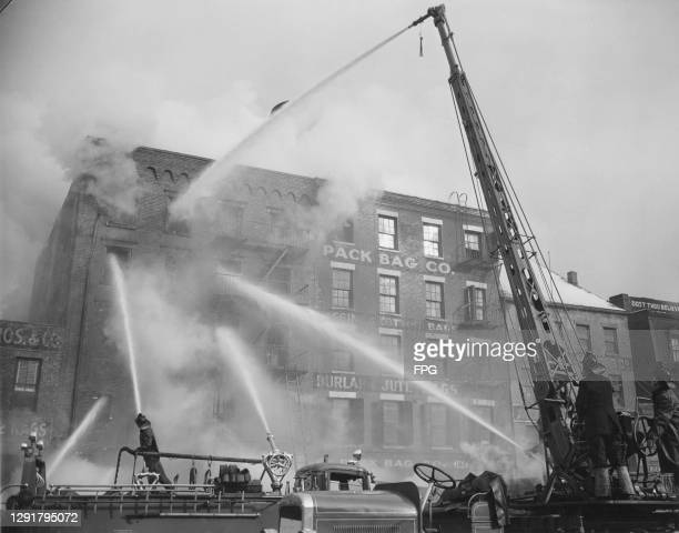 Firefighters tackle a blaze at a paper warehouse at 184 South Street in New York City, New York, February 1947. In addition to hoses, the...