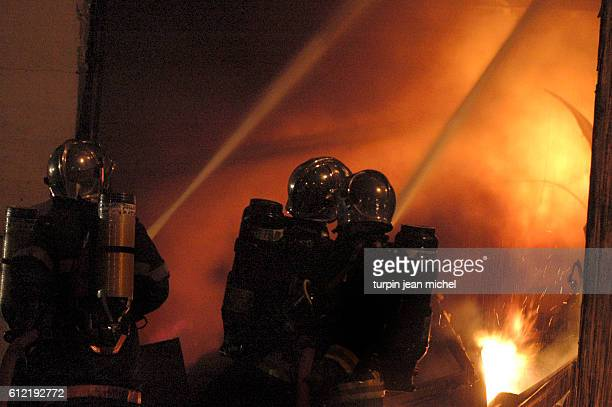 Firefighters tackle a blaze at a warehouse in Asnieres as rioting and civil disorder continues unabated for the 11th consecutive night in the Paris...