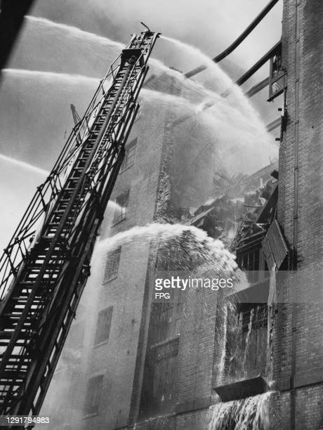 Firefighters tackle a blaze at a warehouse on Colonial Wharf in Wapping, east London, England, 27th September 1935. The fire which wrecked the...